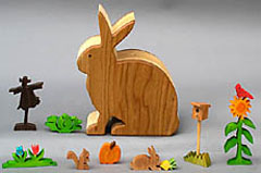 wooden animals, flowers and vegetables in a rabbit box